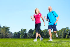 Jogging couple. Senior couple jogging in park. Health and fitness royalty free stock photography