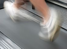 Jogging on exercise treadmill. Man jogging on exercise treadmill in local gym stock image