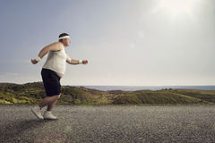 Jogging. Funny overweight man jogging on the road royalty free stock photos