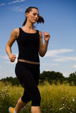 Jogging girl 2. A woman jogging cross country Stock Photography