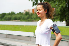 Jogging girl in the city listing music by headphones Royalty Free Stock Photo