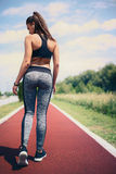 Jogging Girl Slowing Down after Running. Young Sports Woman on Jogging Track Royalty Free Stock Photography
