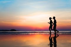 Jogging and healthy lifestyle, two runners silhouettes at sunset, workout and sport. Jogging and healthy lifestyle, two runners silhouettes on the beach at stock images