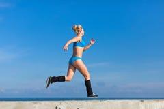 jogging La deportista joven en ropa de deportes azul corre a lo largo de seafron fotos de archivo libres de regalías