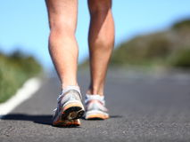 Jogging man. Running shoes and legs of male runner outside on road royalty free stock photo
