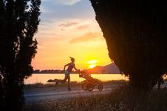 Jogging mother with stroller enjoying motherhood at sunset lands. Running mother with child in stroller enjoying motherhood at sunset and mountains landscape Royalty Free Stock Images