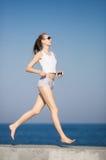 jogging Muchacha alta delgada que corre a lo largo de la playa imagen de archivo libre de regalías