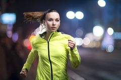 Jogging at night. Young woman jogging at night in the city royalty free stock photos