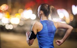 Jogging at night. Young woman jogging at night in the city stock photography
