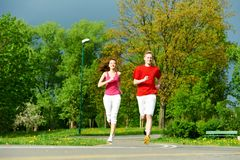 Couple jogging and running outdoors in nature stock photo