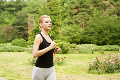 Jogging in park. A young girl jogging in the green park outdoors stock image