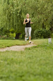 Jogging in park. A young girl jogging on the alley in the green park outdoors stock photography