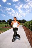 Jogging in the Park. Middle aged woman jogging in the park royalty free stock image