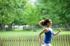 Jogging in the park with earphones Stock Photography