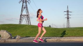 Jogging in park. Slow motion. Jogging in park, sport workout outdoors, sport woman running, woman runner running on open road in countryside, female jogger stock footage