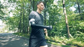 Jogging person with bionic prosthetic hand. Human with a robot arm. A disabled man with bionic prosthesis workouts outdoors