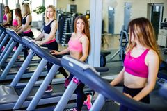 Jogging with pleasure. Side view of young beautiful women looking at each other with smile while running on treadmill at gym. Stock Photography
