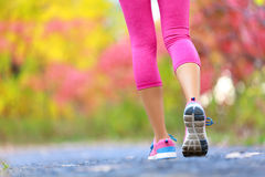 Jogging and running woman with athletic legs. On jog or run on trail in forest in healthy lifestyle concept with close up on running shoes. Female athlete stock image