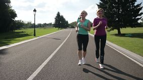 Jogging senior women running parkway in sportswear stock video footage