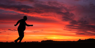 Jogging. Silhouette of funny overweight man jogging at the sunset stock images