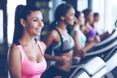 Jogging with smile. Side view close up of young beautiful women looking away with smile while running on treadmill at gym Royalty Free Stock Images