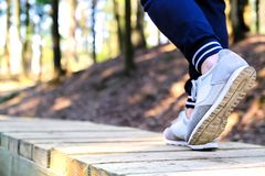 Jogging in sneakers on the bridge in the Park. Sport, Health and physical culture concept royalty free stock images