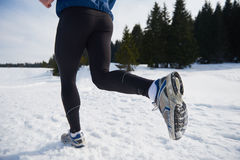 Jogging on snow in forest Royalty Free Stock Photography