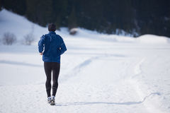 Jogging on snow in forest Royalty Free Stock Image