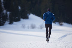 Jogging on snow in forest Stock Images