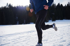 Jogging on snow in forest Stock Photography