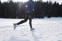 Jogging on snow in forest Royalty Free Stock Photo