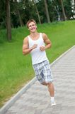 Jogging sport man. Young positive man jogging in park outdoors Stock Photography