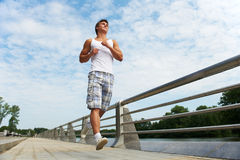 Jogging sport man. Young positive man jogging in park outdoors Stock Photos