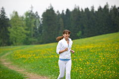 Jogging - sportive woman running in park Royalty Free Stock Images