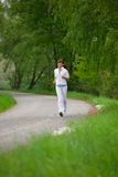 Jogging - sportive woman running on road in nature Royalty Free Stock Photos