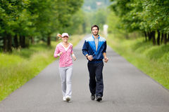 Jogging sportive young couple running park road. Jogging young fit couple running park road in sportswear tracksuit Stock Images