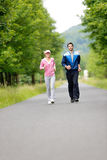 Jogging sportive young couple running park road. Jogging young fit couple running park road in sportswear tracksuit Stock Photos