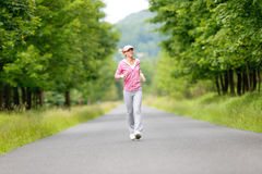 Jogging sportive young woman running park road Stock Photos