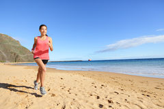 Jogging sports athlete runner woman on beach. Jogging sports athlete runner woman running on beach sweating. Fit exercising female fitness model working out stock images