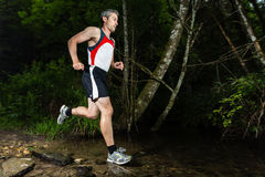 Jogging through a streambed Stock Image