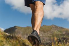 Strong man legs walking on trail in the mountains royalty free stock photography