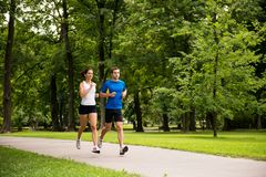 Jogging together - young couple running. Sport couple - young men and women jogging outdoor in nature royalty free stock photos