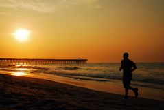 Jogging towards dunrise and a new day. A Jogger Runs Along the Shore at Myrtle Beach at sunrise Stock Image