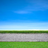 Jogging track. Roadside view, grass and green fence on blue sky Royalty Free Stock Photography