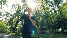 Jogging training of a teenager with a prosthetic hand. Futuristic human cyborg concept. Slow motion footage of jogging training of a teenager with a prosthetic