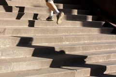 Jogging up the stairs with long shadows Royalty Free Stock Photography