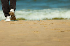 Jogging walking. Female legs hiking on the beach. Stock Photos