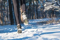 Jogging in winter. running through the snow. run forest snow. Girl in winter sneakers running through the snow stock image