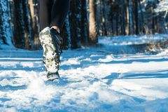 Jogging in winter. running through the snow. run forest snow. Girl in winter sneakers running through the snow stock photos