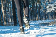 Jogging in winter. running through the snow. run forest snow. Ngirl in winter sneakers running through the snow royalty free stock image